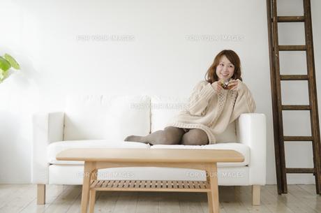 ソファの上でくつろぐ女性の素材 [FYI01076903]