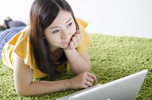床に寝そべってノートパソコンを操作する女性の素材 [FYI01076906]