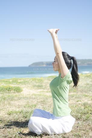 青空と海をバックにストレッチをする女性の素材 [FYI01076907]