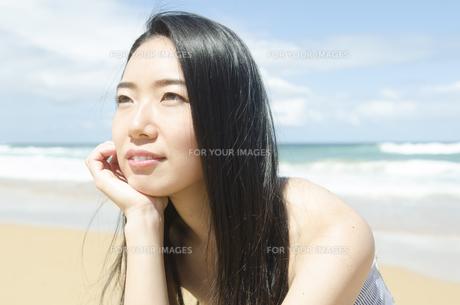 ビーチで頬杖を付いて遠くを見つめる黒髪の女性の素材 [FYI01076916]