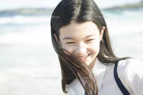 ビーチで笑う制服姿の女の子の素材 [FYI01076917]