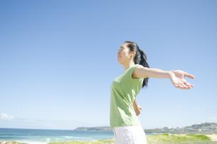 青空と海をバックに深呼吸をする女性の素材 [FYI01076919]