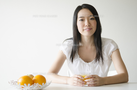 テーブルでオレンジジュースのコップを触る女性の素材 [FYI01076922]