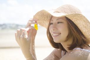 帽子を被り黄色い花を見つめる女性の素材 [FYI01076925]