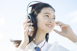 制服姿でヘッドフォンを着けた女の子の素材 [FYI01076931]