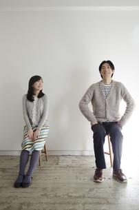 イスに座って笑うカップルの素材 [FYI01076932]