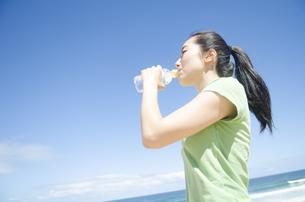 海をバックに水を飲む女性の素材 [FYI01076933]
