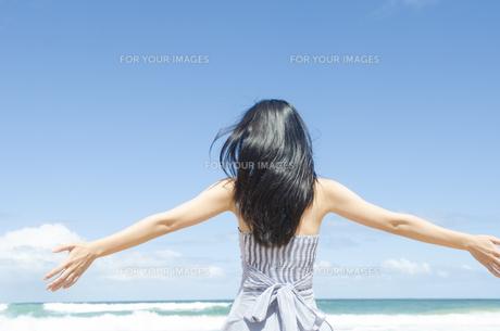 ビーチで手を広げる黒髪の女性の素材 [FYI01076936]