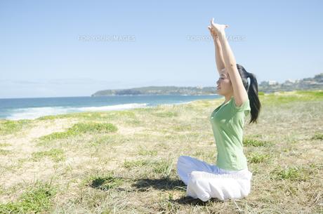 青空と海をバックにストレッチをする女性の素材 [FYI01076942]