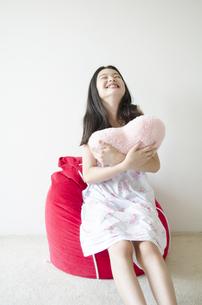 ハートのクッションを抱きしめるパジャマ姿の少女の素材 [FYI01076946]