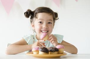カップケーキを持って笑うハーフの女の子の素材 [FYI01076947]