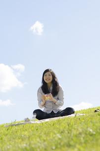 芝生の上でサンドイッチを持って笑顔の女性の素材 [FYI01076949]