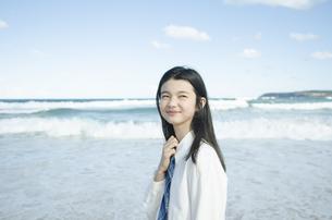 ビーチで遠くを見つめる制服姿の女の子の素材 [FYI01076955]