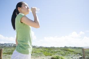 青空と緑をバックに水を飲む女性の素材 [FYI01076956]