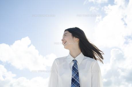 笑顔で遠くを見る制服姿の女の子の素材 [FYI01076960]