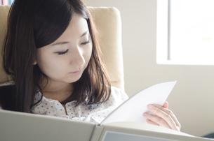 イスに座って本を読む女性の素材 [FYI01076962]