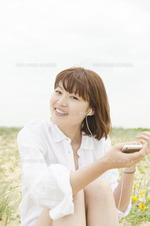 砂浜に座りスマートフォンで音楽を聴く女性の素材 [FYI01076972]