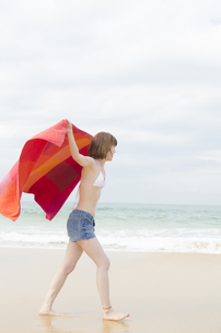 ビーチでタオルを広げて歩くビキニ姿の女性の素材 [FYI01076974]