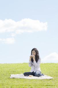 芝生の上でサンドイッチを食べる女性の素材 [FYI01076977]