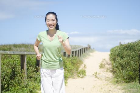 ビーチでジョギングをするポニーテールの女性の素材 [FYI01076979]