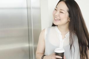 エレベーター前でコーヒーカップを持って笑うOLの素材 [FYI01076984]