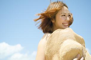 帽子を持って青空バックに笑う女性の素材 [FYI01076985]