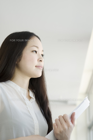書類を手に持って遠くを見つめる女性の素材 [FYI01076987]