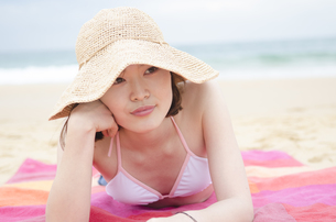 帽子をかぶってビーチに寝そべるビキニ姿の女性の素材 [FYI01076989]