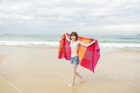 ビーチでタオルを広げて歩くビキニ姿の女性の素材 [FYI01076990]