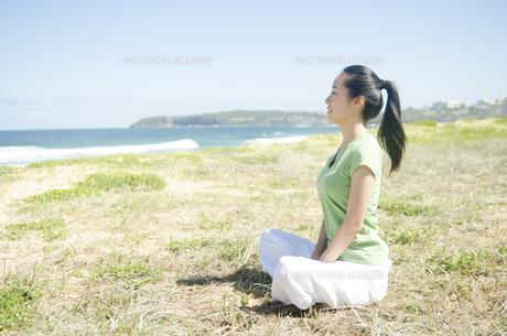 青空と海をバックにあぐらをかく女性の素材 [FYI01076992]