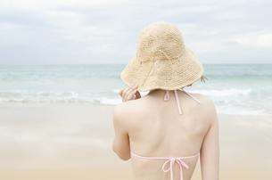 帽子をかぶってビーチにたたずむビキニ姿の女性の後姿の素材 [FYI01076993]
