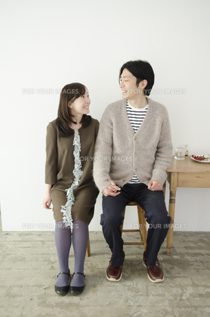 室内で座って見つめ合うカップルの素材 [FYI01076994]