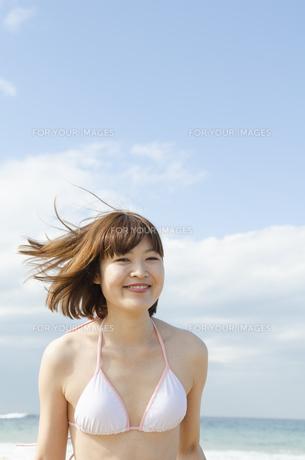 ビーチで微笑むビキニ姿の女性の素材 [FYI01076995]