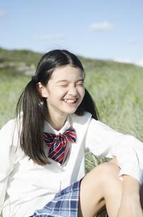 制服姿で草原に座って笑う女の子の素材 [FYI01076996]