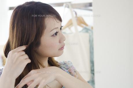 部屋の中で髪を整える女性の素材 [FYI01076998]