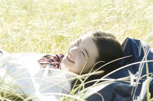 制服姿で草原に寝転がって笑う女の子の素材 [FYI01077001]