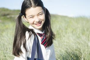 制服姿で草原に座って笑う女の子の素材 [FYI01077002]