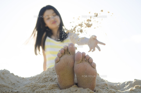 ビーチで砂を自分の足に掛ける女の子の素材 [FYI01077004]