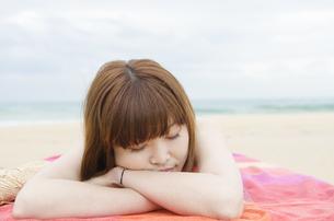 ビーチに寝そべって眠る女性の素材 [FYI01077018]