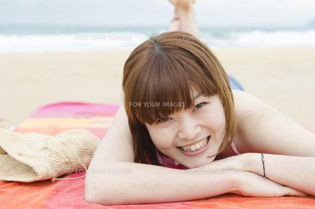 ビーチに寝そべって笑うビキニ姿の女性の素材 [FYI01077025]