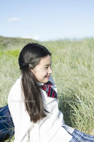 制服姿で草原に座る女の子の素材 [FYI01077026]