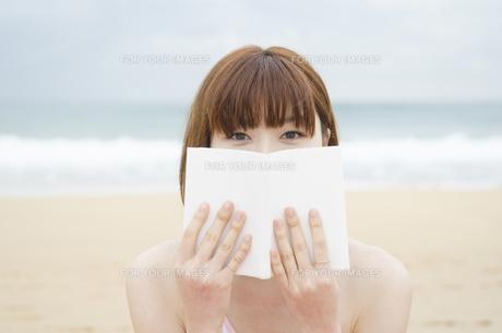ビーチに座って本で顔を隠す女性の素材 [FYI01077027]