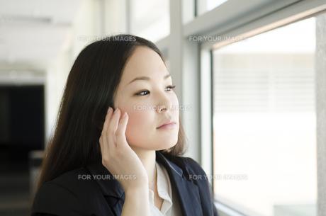 頬に手を添えて窓の外を見る女性の素材 [FYI01077029]