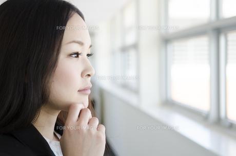 あごに手を添えて外を見る女性の素材 [FYI01077041]