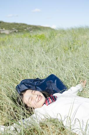 制服姿で草原に寝転がって手を広げる女の子の素材 [FYI01077044]