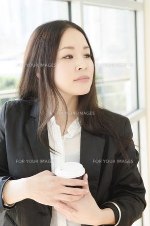 コーヒーカップを手にしたスーツ姿の女性の素材 [FYI01077047]