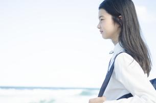 ビーチでたたずむ制服姿の女の子の素材 [FYI01077049]