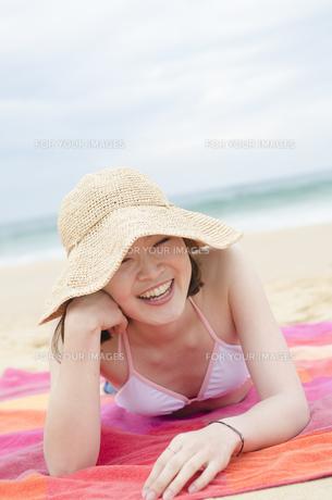 帽子をかぶってビーチに寝そべって笑うビキニ姿の女性の素材 [FYI01077051]