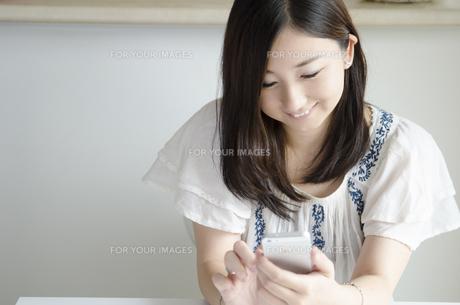 部屋の中でスマートフォンを操作する女性の素材 [FYI01077055]
