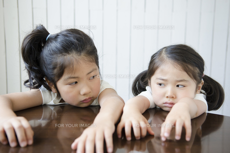 机に腕を乗せてにらみ合う姉妹の素材 [FYI01077057]